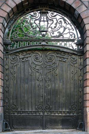 puertas de hierro: antiguo muro de piedra con puerta de metal forjado