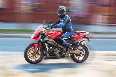 Rider on motorcycle rides on city street