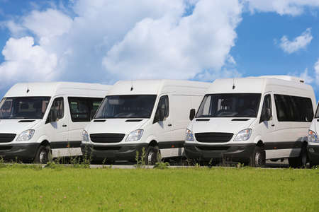 transportations: number of new white minibuses and vans outside Stock Photo