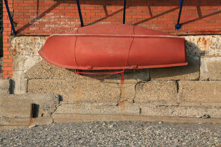 attached: orange lifeboat attached to concrete wall Stock Photo
