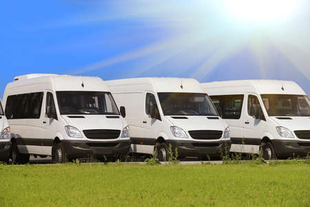 vans: number of new white minibuses and vans outside Stock Photo