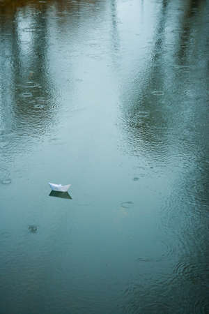 paper boat: origami boat on wet asphalt during rain in summer