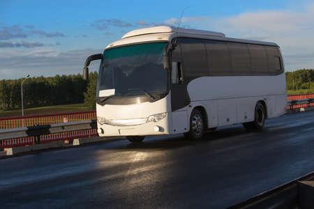 Witte toeristische bus gaat op de brug naar zonsondergang Stockfoto