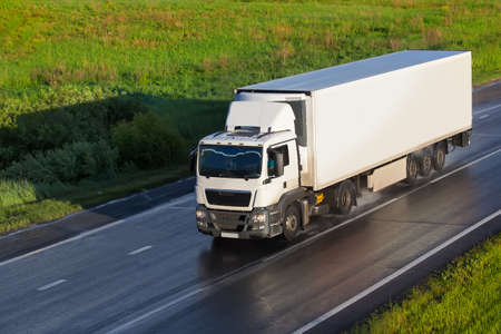 big powerful truck moves on highway Stock Photo