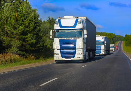 escort of trucks moves on the country highway