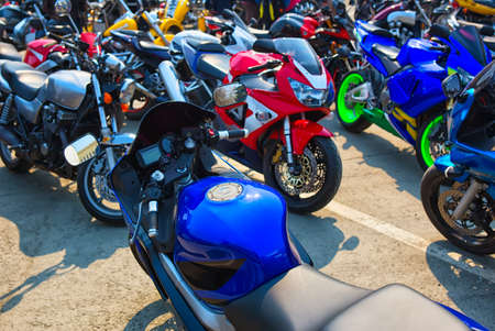 MOTORCYCLES: many motorcycles on parking on asphalt  close up