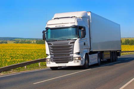 grote witte vrachtwagen gaat op de snelweg langs het veld met zonnebloemen