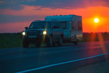 SUV with the tourist trailer at sunrise Banco de Imagens