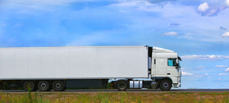 cargo: white truck transports freight on the country highway Stock Photo
