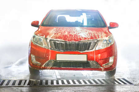 car covered with foam on car wash 스톡 콘텐츠