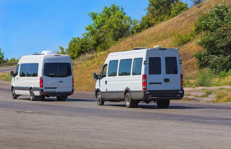 mini: white minibuses go on the twisting road in the summer