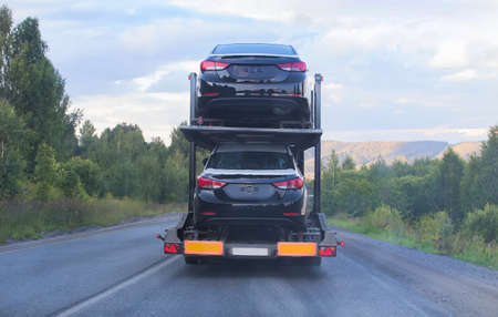 semitruck: transportation of car on semi-trailer on country highway Stock Photo