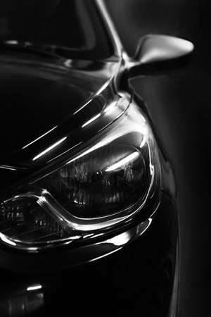 black car: black car in patches of light on black background Stock Photo
