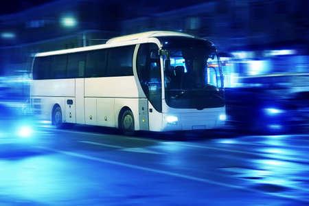 bus turístico se mueve en la noche de la ciudad Foto de archivo