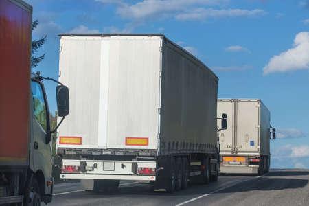 tilt: escort of trucks moves on mountain road Stock Photo
