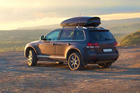 terrain: trip on SUV in hilly terrain on sunset