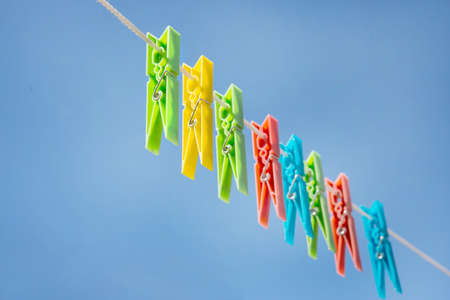 clothespegs: color plastic clothespegs on rope against sky