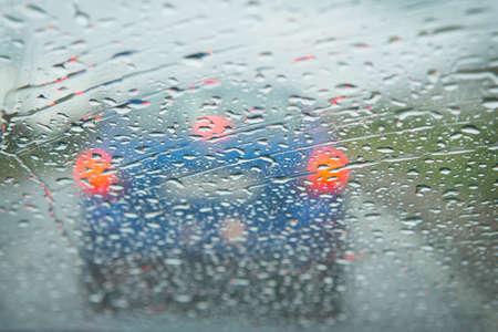 go inside: rain on the city street through a car windshield