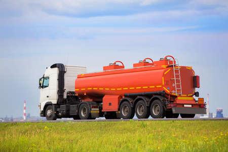camión cisterna: gran camión de gas del tanque va en la carretera contra el cielo