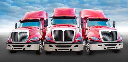 Drie grote rode vrachtwagen op de weg Stockfoto
