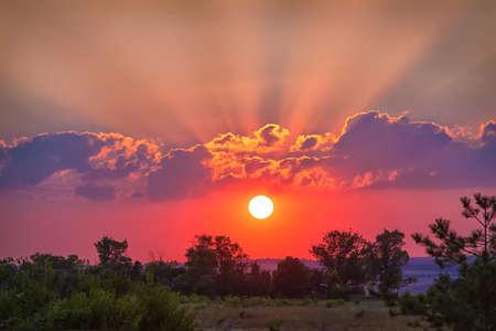 sunset sky: beautiful sunset in cloudy sky over field