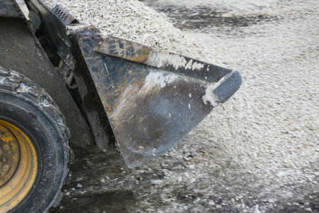 steel works: loader pours out crushed stone from ladle close up