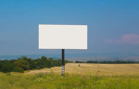 road shoulder: White rectangular billboard near road against the sky