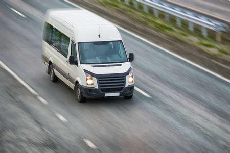 petit bus blanc va sur la route dans la soirée
