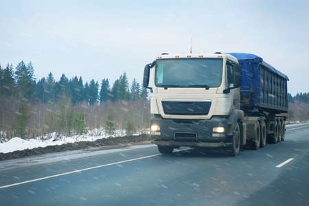 a blizzard: truck goes on winter road to blizzard