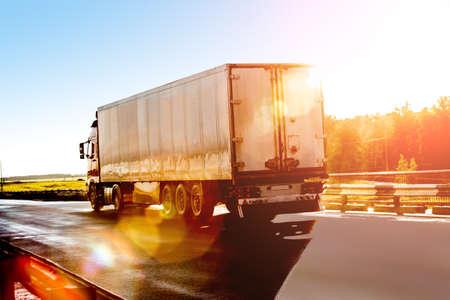camion: camión grande va en la carretera a la salida del sol Foto de archivo