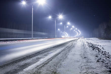 country road: winter highway at night shined with lamps Stock Photo