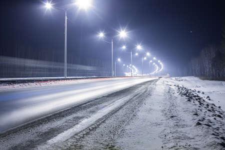 Winterse snelweg 's nachts geschonken met lampen Stockfoto