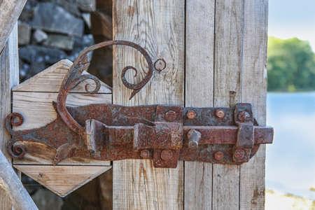 door bolt: ancient metal bolt on wooden door outdoors