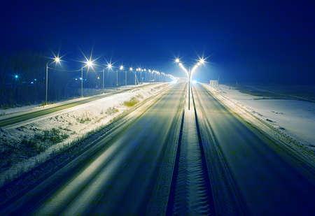 Winterlandstraße in der Nacht glänzte mit Lampen Standard-Bild - 53680637