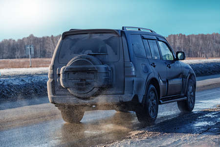 slow lane: dirty SUV goes in winter on  highway