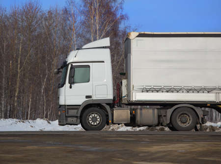 driving conditions: big truck goes on the winter snow highway