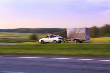 car with trailer moves on highway in evening