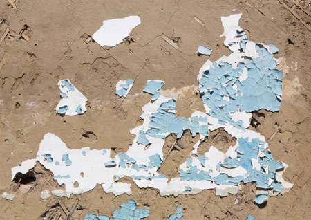 concrete surface finishing: old wall with cracked white and blue paint