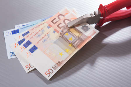 euro banknotes clamped in flat-nose pliers close up Stock Photo