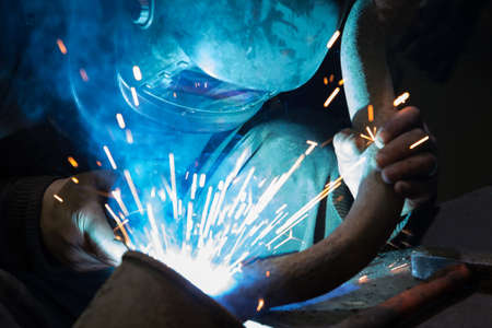 welds: welder in mask welds metal details Stock Photo
