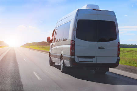 minibus goes on the country highway along the wood