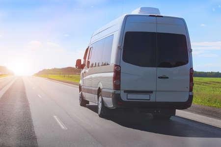 minibus gaat op het land snelweg langs het hout Stockfoto
