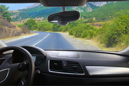 driving a car: view from salon of car going on the mountain road Stock Photo