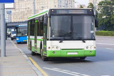 autobuses urbanos blanco va a lo largo de la calle Foto de archivo