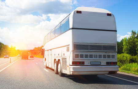 tourist bus goes on highway in beams of sun Stock Photo