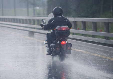 motorcyclist moves on motorcycle on highway to rainy weather