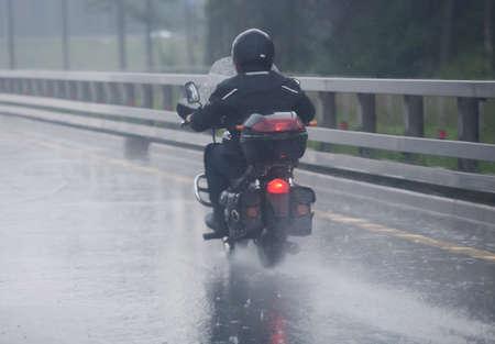 Motorrijder beweegt op motorfiets op de snelweg naar regenachtig weer