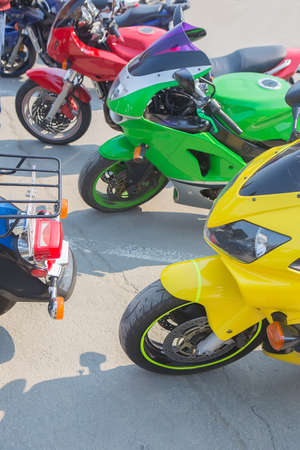 red green and yellow motorcycle in parking lot in row close up
