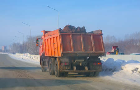 dampness: Truck transports soil on winter snow-covered road