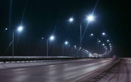 carretera de invierno en la noche brilló con lámparas